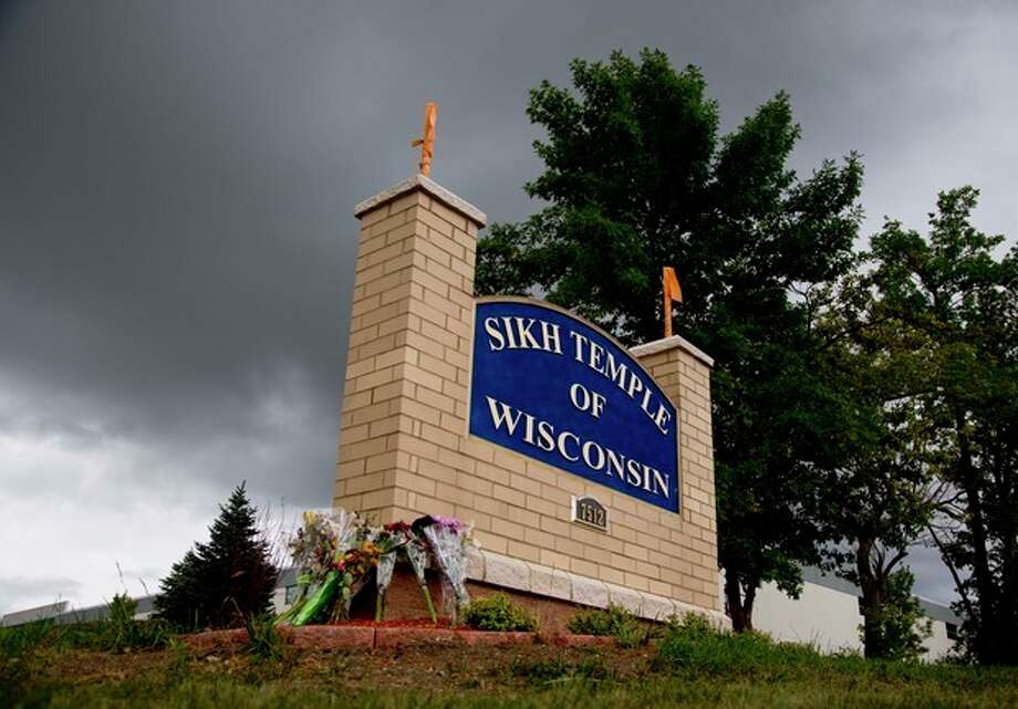 Flowers lie on the sign to the Sikh temple of Wisconsin where members were allowed to re-enter for the first time in Oak Creek, Wis., Thursday, Aug 9, 2012. The mass shooting last Sunday claimed six members of the temple. (AP Photo/Jeffrey Phelps) / FR59249 AP
