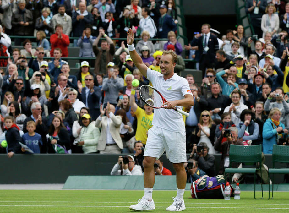 Steve Darcis of Belgium waves to spectators after winning against Rafael Nadal of Spain in their Men's first round singles match at the All England Lawn Tennis Championships in Wimbledon, London, Monday, June 24, 2013. (AP Photo/Kirsty Wigglesworth) / AP