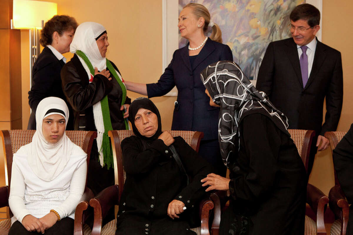 Turkey's Foreign Minister Ahmet Davutoglu, top right, and U.S. Secretary of State Hillary Rodham Clinton meet with Syrian refugees in Istanbul, on Saturday, Aug. 11, 2012. (AP Photo/Jacquelyn Martin, Pool)