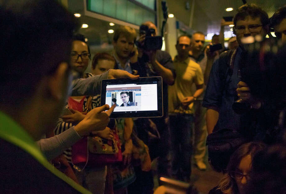 """Journalists show passengers arriving from Hong Kong a tablet with a photo of Edward Snowden, a former CIA employee who leaked top-secret documents about sweeping U.S. surveillance programs, at Sheremetyevo airport, just outside Moscow, Russia, Sunday, June 23, 2013. The former National Security Agency contractor wanted by the United States for revealing two highly classified surveillance programs has been allowed to leave for a """"third country"""" because a U.S. extradition request did not fully comply with Hong Kong law, the territory's government said Sunday. (AP Photo/Alexander Zemlianichenko) / AP"""