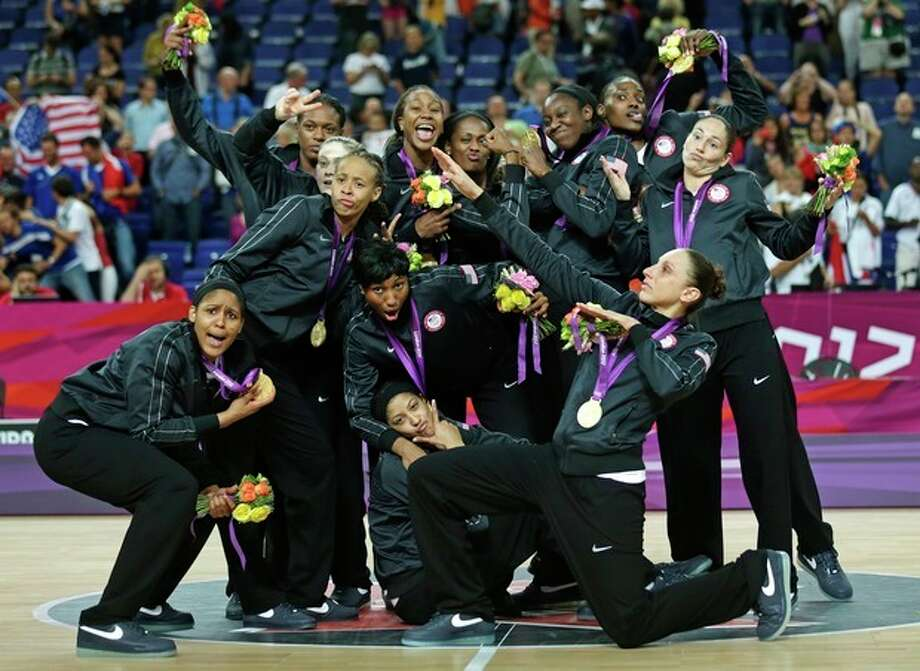United States' poses with their gold medals at center court after beating France during the women's gold medal basketball game at the 2012 Summer Olympics, Saturday, Aug. 11, 2012, in London. (AP Photo/Charles Krupa) / AP