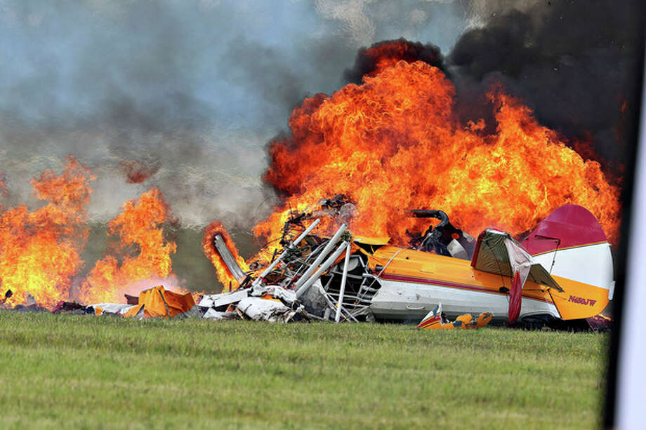 Flames erupt from a plane after a stunt plane crashed while performing with a wing walker at the Vectren Air Show, Saturday, June 22, 2013, in Dayton, Ohio. The crash killed the pilot and the wing walker instantly, authorities said. (AP Photo/Thanh V Tran) / AP