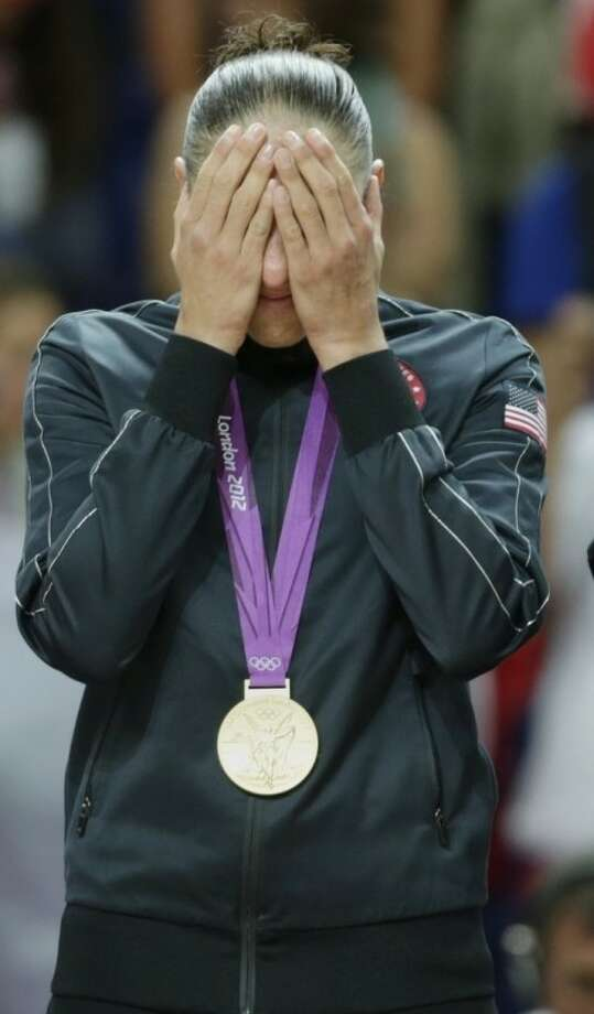 United States' Diana Taurasi holds her hands to her face after being presented with her gold medal after beating France in the women's gold medal basketball game at the 2012 Summer Olympics, Saturday, Aug. 11, 2012, in London. (AP Photo/Charles Krupa)