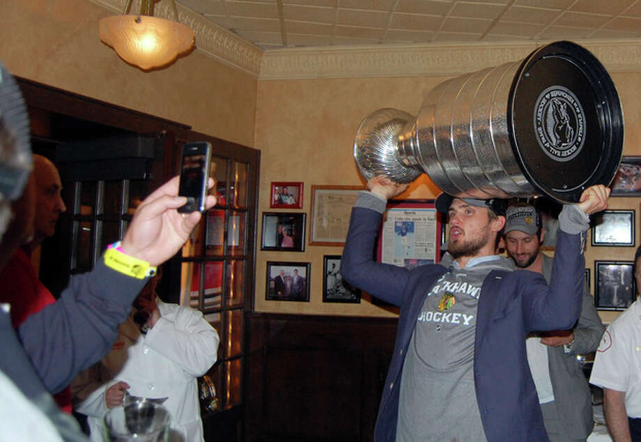 In this photo provided by Harry Caray's Restaurant Group, Chicago Blackhawks' Niklas Hjalmarsson, of Sweden, hoists the Stanley Cup for fans inside Harry Caray's in Rosemont, Ill., Tuesday morning, June 25, 2013, after the team arrived home from Boston following their Stanley Cup hockey final win over the Boston Bruins. (AP Photo/Harry Caray's Restaurant Group) / Harry Caray's Restaurant Group