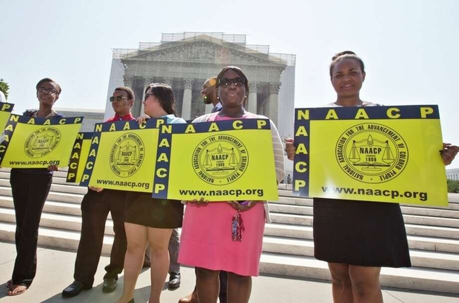 Representatives from the NAACP Legal Defense Fund stand outside the Supreme Court in Washington, Tuesday, June 25, 2013, awaiting a decision in Shelby County v. Holder, a voting rights case in Alabama. The Supreme Court says a key provision of the landmark Voting Rights Act cannot be enforced until Congress comes up with a new way of determining which states and localities require close federal monitoring of elections. (AP Photo/J. Scott Applewhite) / AP