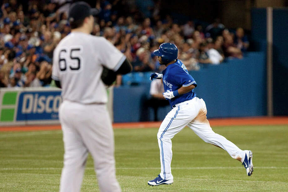Toronto Blue Jays' Edwin Encarnacion, right, rounds the bases after hitting a two-run home run off New York Yankees pitcher Phil Hughes during the fourth inning of a baseball game, Sunday, Aug. 12, 2012, in Toronto. (AP Photo/The Canadian Press, Chris Young) / The Canadian Press