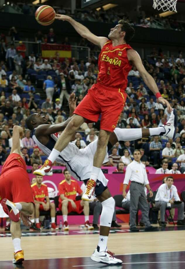 United States' Kevin Durant is fouled as he goes up for a shot against Spain's Rudy Fernandez during the men's gold medal basketball game at the 2012 Summer Olympics, Sunday, Aug. 12, 2012, in London. (AP Photo/Charles Krupa)