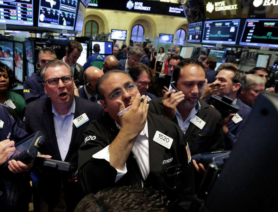 FILE - In this Friday, June 21, 2013 file photo, traders gather at the post on the floor of the New York Stock Exchange that handles Pfizer and Zoetis. Stock and bond prices are sinking because investors were caught off guard and alarmed by the Federal Reserve's signal that long-term interest rates are headed higher. (AP Photo/Richard Drew, File) / AP