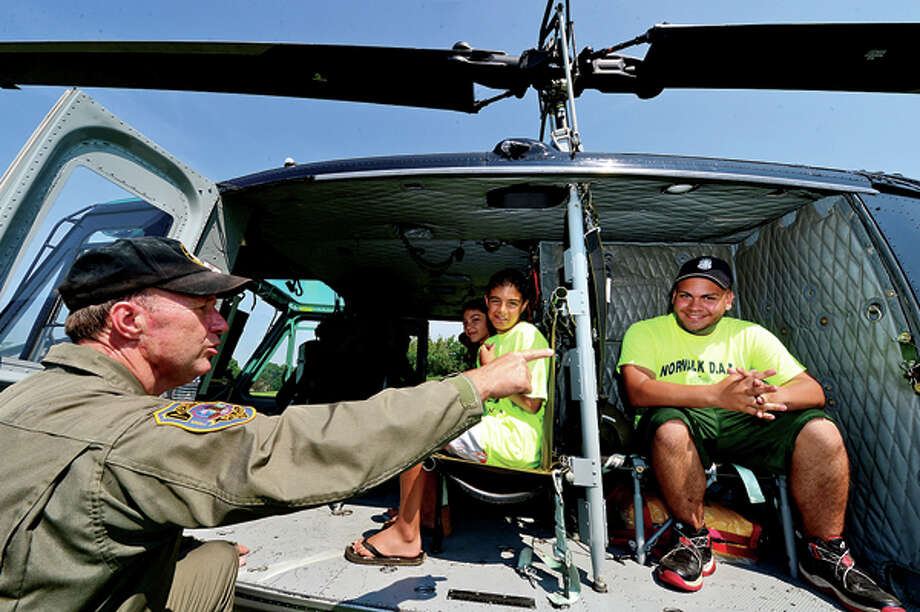 Retired Detective Lt. Bob Hettrick leads DARE campers including James Cirifalco and counselor Eric Aldarondo in a tour of a police helicopter at Taylor Farm Park Tuesday as part of the Norwalk police summer camp. Hour photo / Erik Trautmann / (C)2013, The Hour Newspapers, all rights reserved