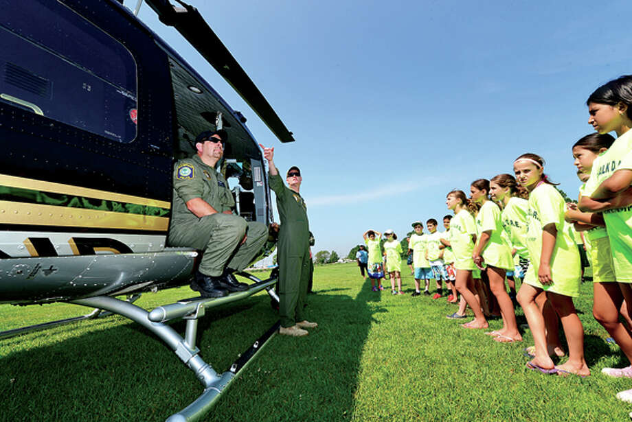 Officer Mark Lecardo and Captain Alan Wilcoxson of the Stratford police department lead DARE campers in a tour of a police helicopter at Taylor Farm Park Tuesday as part of the Norwalk police summer camp. Hour photo / Erik Trautmann / (C)2013, The Hour Newspapers, all rights reserved