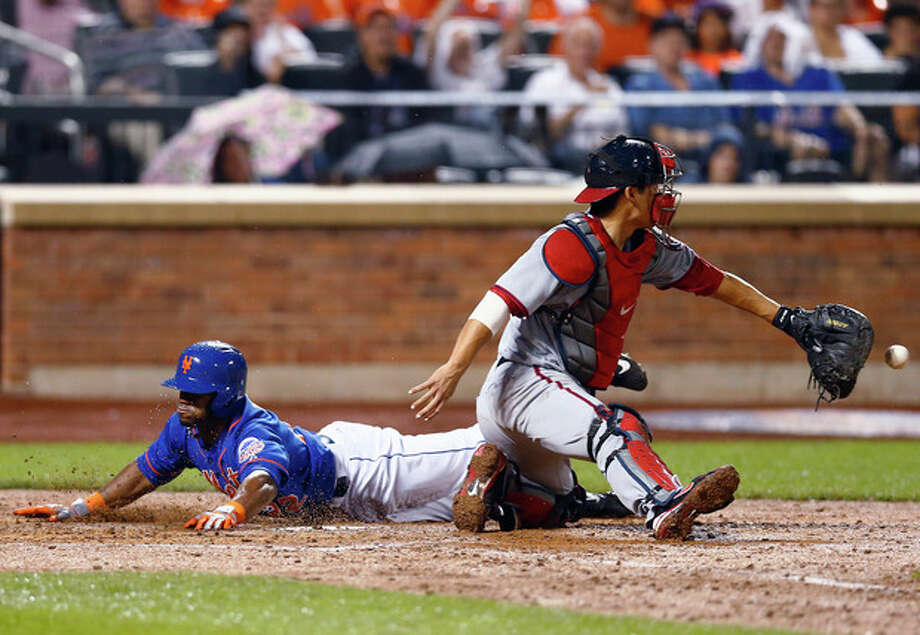 New York Mets Eric Young Jr. (22) slides home safely on a double by Marlon Byrd as Washington Nationals catcher Kurt Suzuki fields the late throw in the fifth inning of a baseball game in New York, Friday, June 28, 2013. (AP Photo/Paul J. Bereswill) / FR168017 AP