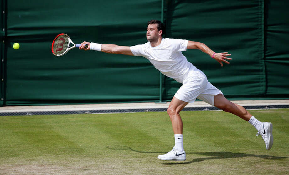 Grigor Dimitrov of Bulgaria stretches to return to Grega Zemlja of Slovenia during their Men's second round singles match at the All England Lawn Tennis Championships in Wimbledon, London, Thursday, June 27, 2013. (AP Photo/Sang Tan) / AP