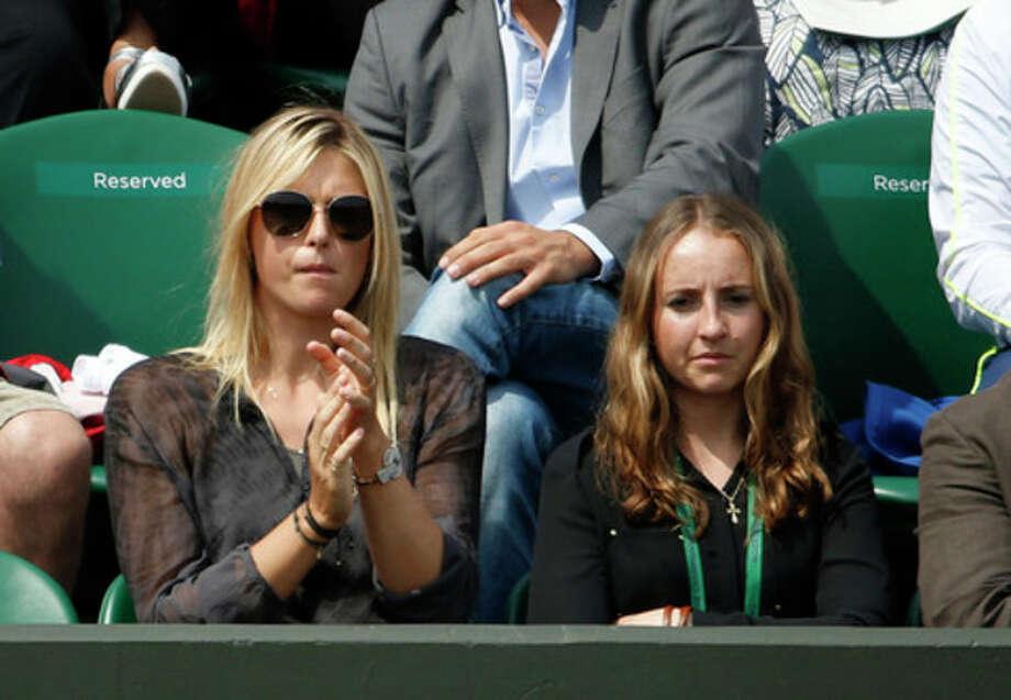 Maria Sharapova of Russia, left, applauds as she watches her boyfriend Grigor Dimitrov of Bulgaria as he plays Grega Zemlja of Slovenia during their Men's second round singles match at the All England Lawn Tennis Championships in Wimbledon, London, Thursday, June 27, 2013. (AP Photo/Sang Tan) / AP
