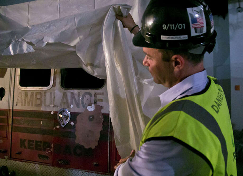 Joe Daniels, 911 Memorial President, lifts the cover for a glance of an ambulance during a tour of the 911 Memorial Museum on Thursday, June 27, 2013 in New York. Recovered from the World Trade Center after September 11, 2001, the vehicle will be part of the museum's permanent installment. (AP Photo/Bebeto Matthews) / AP