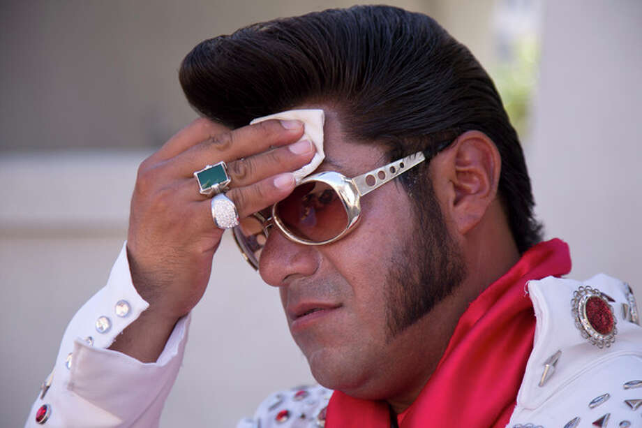 "Elvis impersonator Cristian Morales wipes sweat from his brow while standing out on The Strip posing for photos with tourists, Thursday, June 27, 2013 in Las Vegas. Morales preferred to stand out in the 112 degree heat of the day instead of working the cooler evening hours saying ""We'd much rather fight with the sun than fight with the drunk people."" A high pressure system parking over the West is expected to bring temperatures this weekend and into next week that are extreme even for a region used to baking during the summer. (AP Photo/Julie Jacobson) / AP"
