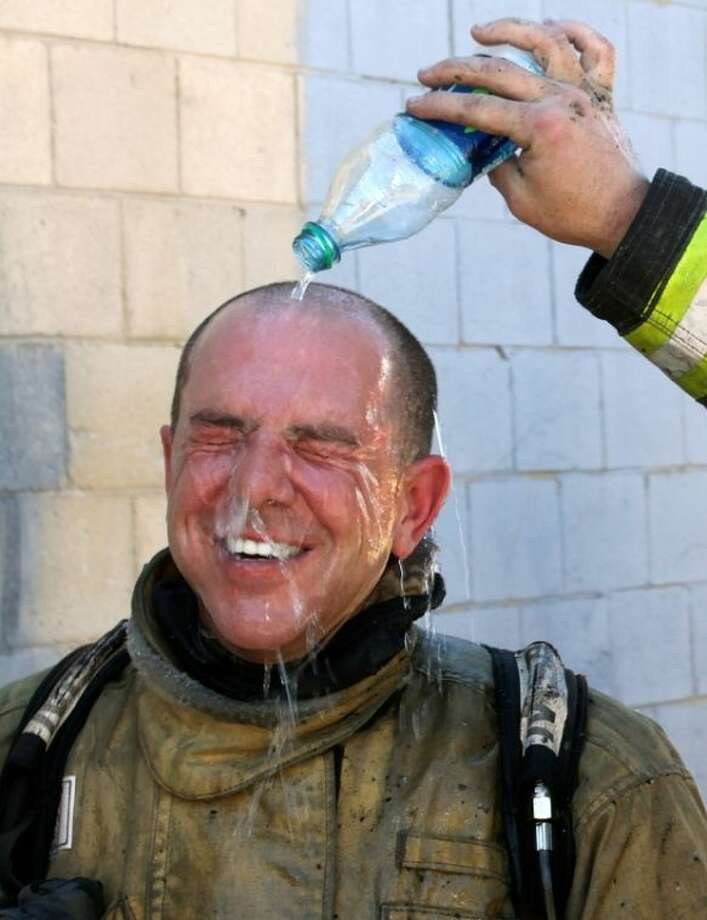 A Salt lake City fireman pours a cold bottle of water over the head of fireman Cary Turner after battling a house fire Thursday, June 26, 2013, in Salt lake City. Temperatures in Utah are approaching record highs and a heat advisory will be in effect for central and western parts of southern Utah through the weekend. The National Weather Service has issued a hazardous weather outlook for the western two-thirds of the state. (AP Photo/Rick Bowmer)