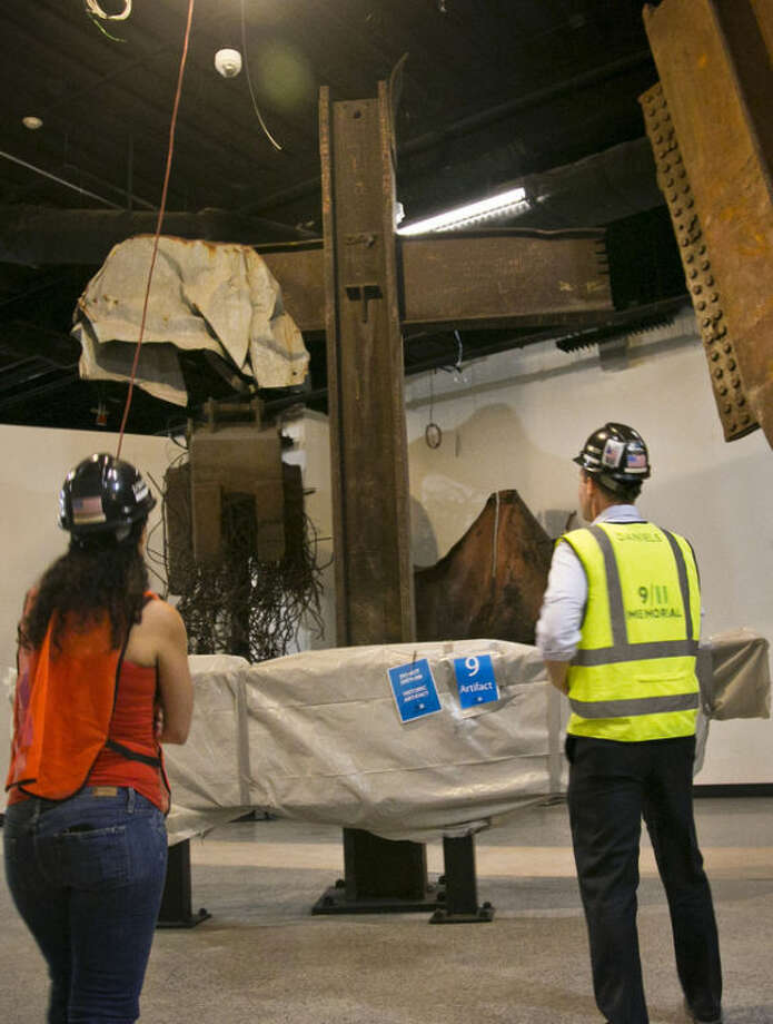 Joe Daniels, right, 911 Memorial President, and Anthoula Katsimatides, left, a member of the 911 Memorial board, approach a steel cross beam recovered from the World Trade Center (WTC) site and installed at the 911 Memorial Museum, Thursday, June 27, 2013 in New York. This 17-foot-tall intersecting steel column and crossbeam was found in the rubble of 6 World Trade Center on September 13, 2001. It has since been perceived as a religious symbol by many, receiving an official ceremonial blessing of the cross. (AP Photo/Bebeto Matthews)