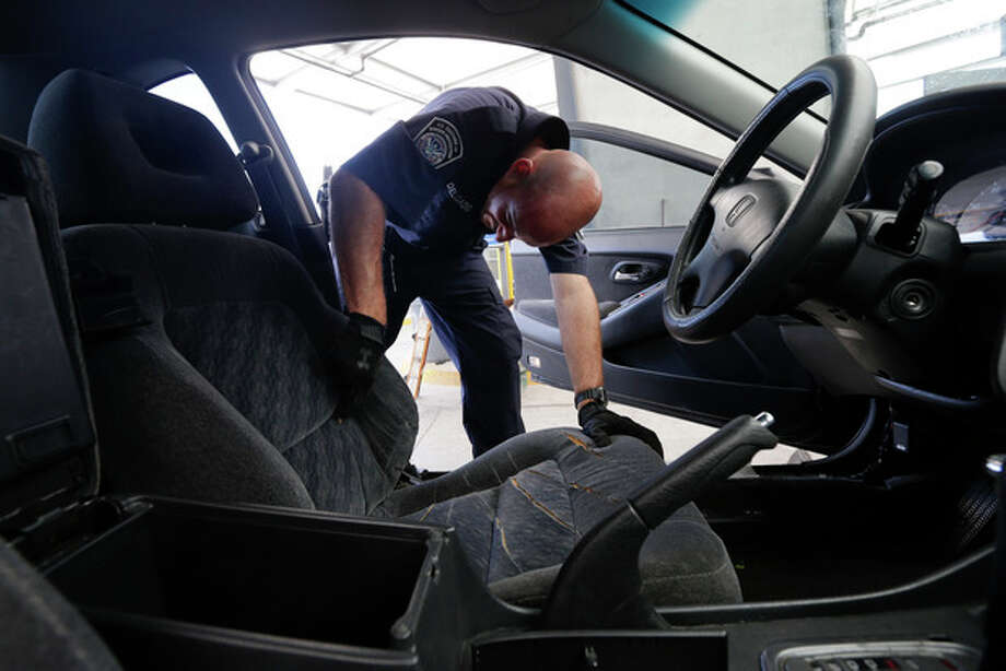 Customs and Border Protection officer Steve Delgado slashes the driver's seat of a Honda Accord with a knife after finding more than 14 pounds of methamphetamine hidden behind the radio at the San Ysidro port of entry Thursday, June 27, 2013, in San Diego. The smuggling of the drug at land border crossings has jumped in recent years but especially at San Diego's San Ysidro port of entry, which accounted for more than 40 percent of seizures in fiscal year 2012. (AP Photo/Gregory Bull) / AP