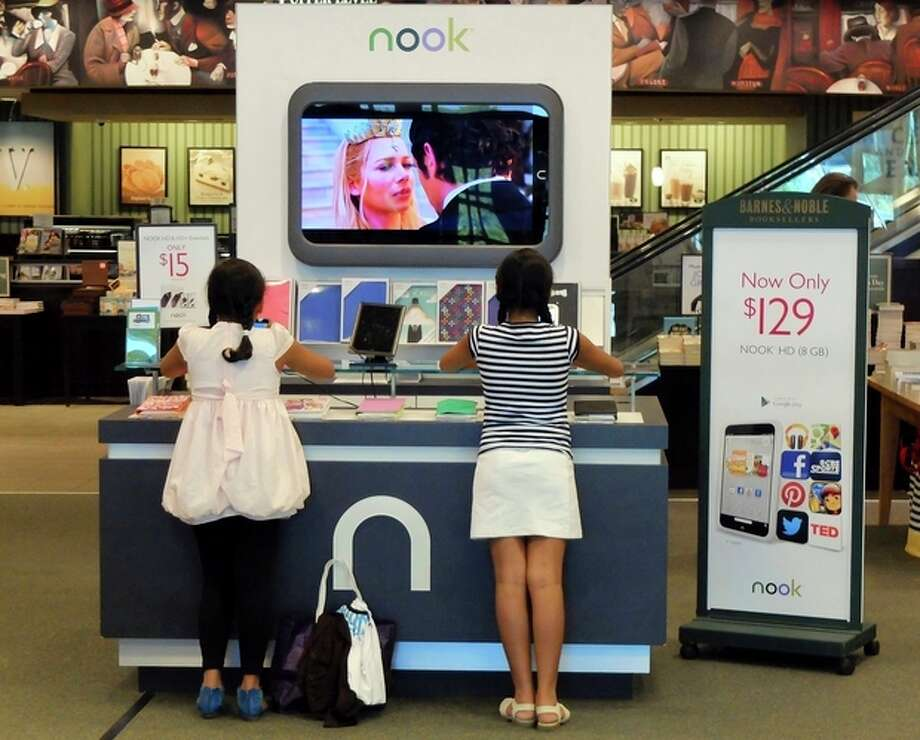 In this Friday, June 21, 2013 photo, customers look at models of the Nook tablet at a Barnes and Noble store in Pineville, N.C. A measure of U.S. consumer confidence remained near a six-year high in June as higher home prices boosted household wealth. The survey shows Americans are feeling better about the economy, despite wild gyrations in the stock market. (AP Photo/Chuck Burton) / AP