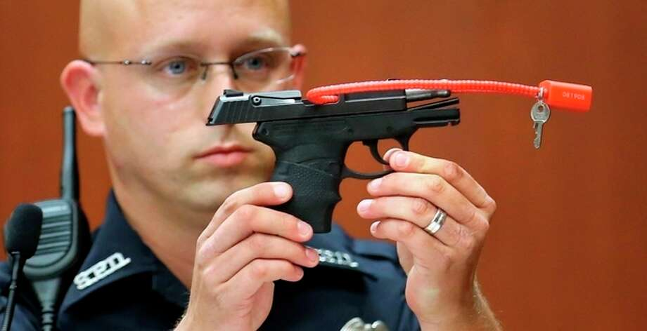 Sanford police officer Timothy Smith holds up the gun that was used to kill Trayvon Martin, while testifying in the 15th day of the George Zimmerman trial, in Seminole circuit court in Sanford, Fla., Friday, June 28, 2013. Zimmerman has been charged with second-degree murder for the 2012 shooting death of Trayvon Martin.(AP Photo/Orlando Sentinel, Joe Burbank, Pool) / Pool Orlando Sentinel