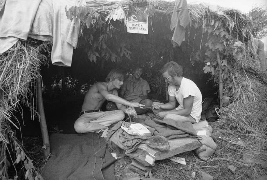 """ADVANCE FOR SUNDAY, JUNE 30 AND THEREAFTER - FILE - This Aug. 17, 1969 black-and-white file photo shows music fans seeking shelter is a grass hut at the Woodstock Music and Art Festival in Bethel, N.Y. where the sign above reads """"Have a Marijuana."""" It took 50 years for American attitudes about marijuana to zigzag from the paranoia of """"Reefer Madness"""" to the excesses of Woodstock back to the hard line of Just Say No. And now, in just a few short years, public opinion has shifted so dramatically toward pragmatic acceptance of marijuana that even those who champion legalization are surprised at how quickly attitudes are changing and states are moving to approve the drug for medical use and just for fun. (AP Photo, File)"""