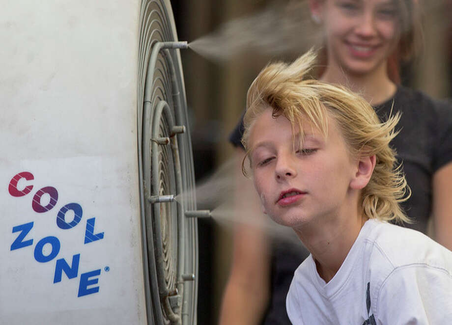 Ten-year-old Easton Martin, of Mesa, Ariz., stops to cool off in a misting fan while walking along The Strip with his family, Friday, June 28, 2013 in Las Vegas. A blazing heat wave expected to send the mercury soaring to nearly 120 degrees in Phoenix and Las Vegas settled over the West on Friday, threatening to ground airliners and raising fears that people and pets will get burned on the scalding pavement. (AP Photo/Julie Jacobson) / AP
