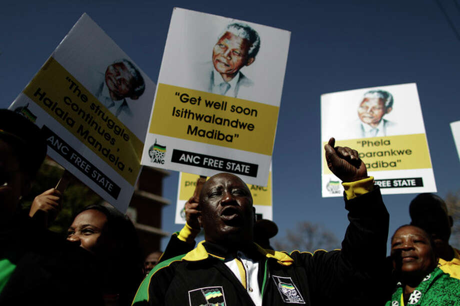 FILE -In this Friday, June 28, 2013, photo, African National Congress (ANC) supporters chant slogans in support of former South African President Nelson Mandela, at the entrance to the Mediclinic Heart Hospital where Mandela is being treated in Pretoria, South Africa. Members of Nelson Mandela's family as well as South African Cabinet ministers visited the hospital on Friday. (AP Photo/Muhammed Muheisen, File) / AP
