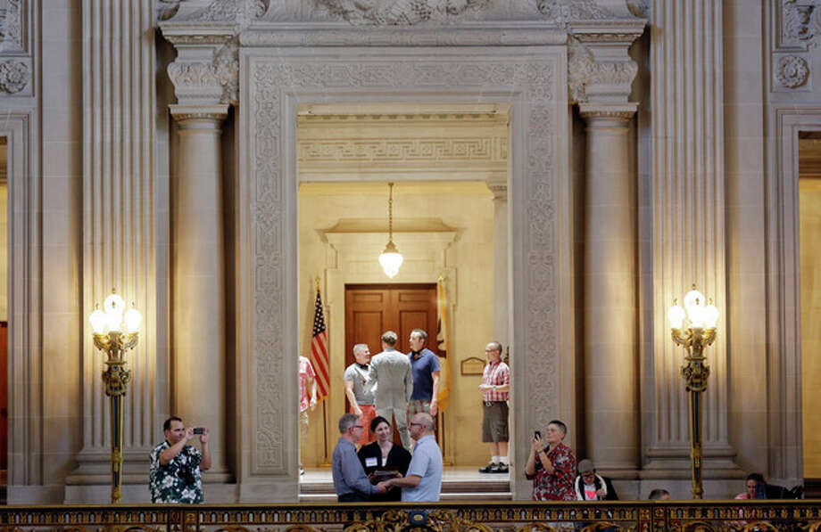 Gay couples, including Andy Uri, in long sleeve shirt, and Joe Taus, bottom center, of Portland, Ore., exchange wedding vows at City Hall in San Francisco, Saturday, June 29, 2013. Dozens of gay couples waited excitedly Saturday outside of San Francisco's City Hall as clerks resumed issuing same-sex marriage licenses, one day after a federal appeals court cleared the way for the state of California to immediately lift a 4 ½ year freeze. Big crowds were expected from across the state as long lines had already stretched down the lobby shortly after 9 a.m. City officials decided to hold weekend hours and let couples tie the knot as San Francisco is also celebrating its annual Pride weekend expected to draw as many as 1 million people. (AP Photo/Marcio Jose Sanchez) / AP
