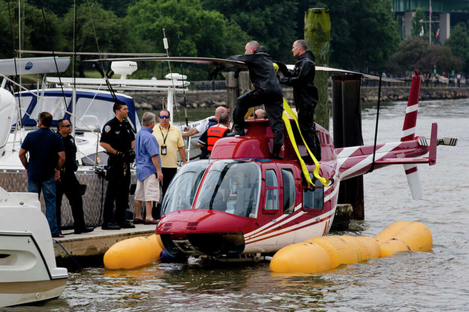 A helicopter rests on a pontoon at the 79th Street Boat Basin after an emergency landing over the Hudson river, Sunday, June 30, 2013, in New York. New York authorities say a helicopter carrying four Swedish tourists landed in the Hudson River off Manhattan Sunday, but everyone has been rescued. (AP Photo/John Minchillo) / FR170537 AP