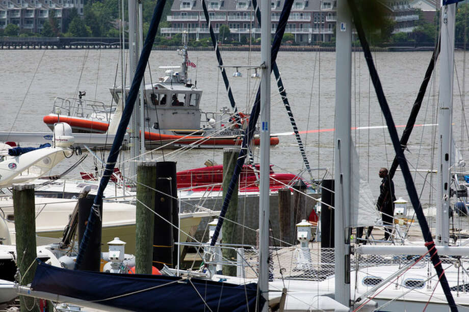 A helicopter rests on a pontoon at the 79th Street Boat Basin after emergency landing over the Hudson river, Sunday, June 30, 2013, in New York. New York authorities say a helicopter carrying four Swedish tourists has landed in the Hudson River off Manhattan, but everyone has been rescued. The incident happened shortly before noon Sunday in the section of the river near 79th Street. The pilot and four passengers were taken to shore. (AP Photo/John Minchillo) / FR170537 AP