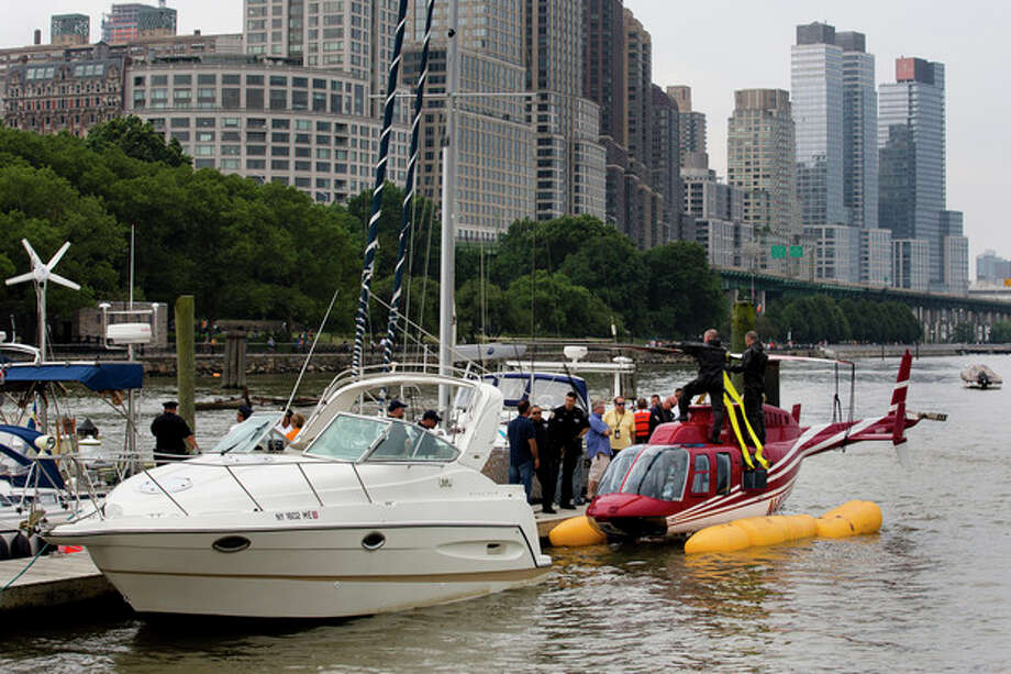 A helicopter rests on a pontoon at the 79th Street Boat Basin after emergency landing over the Hudson river, Sunday, June 30, 2013, in New York. New York authorities say a helicopter carrying four Swedish tourists landed in the Hudson River off Manhattan Sunday, but everyone has been rescued. (AP Photo/John Minchillo) / FR170537 AP