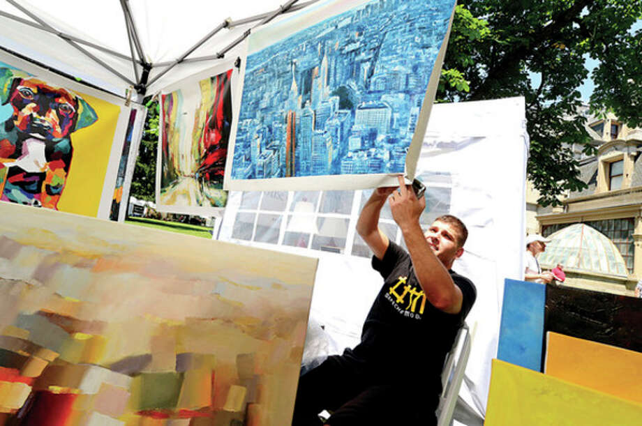 Hour photos / Erik TrautmannAbove, Willy Biaggi hangs his art during the first Norwalk Art Festival at Mathews Park Saturday. Below, Marge Kitchens and Shirlie Kemsek look at the Fantasy Dolls by Kathy Pilipauskas during the art festival. / (C)2013, The Hour Newspapers, all rights reserved