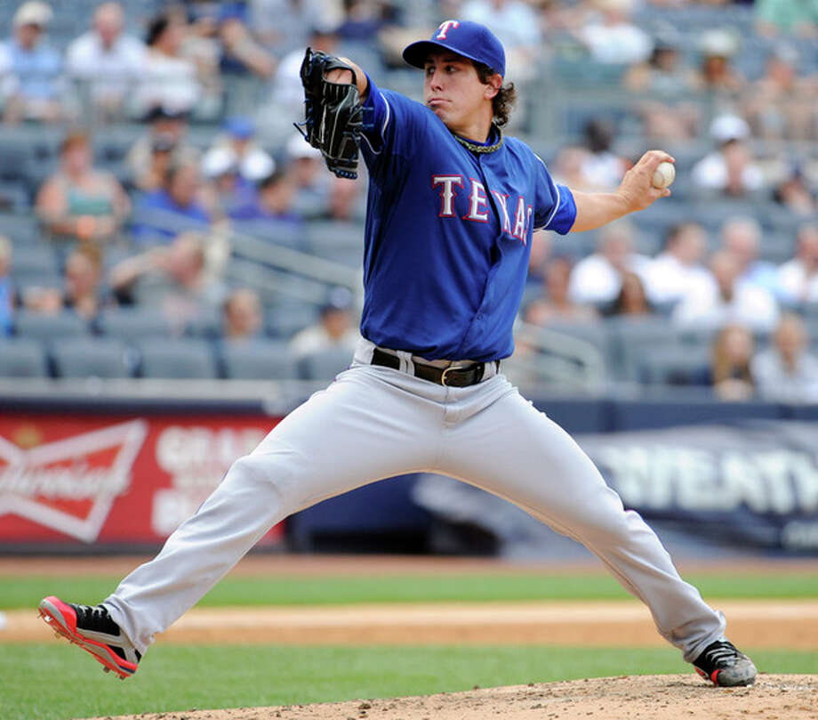 Texas Rangers pitcher Derek Holland delivers the ball to the New York Yankees during the third inning of a baseball game Thursday, June 27, 2013, at Yankee Stadium in New York. (AP Photo/Bill Kostroun) / FR51951 AP