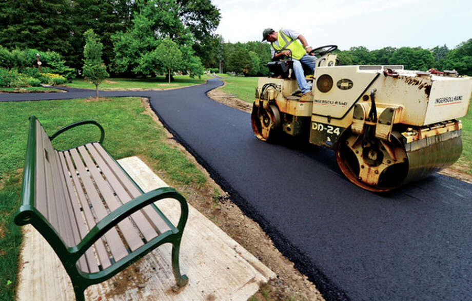 Hour photo / Erik TrautmannWalking solutionsWorkers with Deering Construction install 1,200 linear feet of paved walkway at Cranbury Park Thursday. The park's new walkway will connect the mansion, trail system and Great Lawn and provide handicap accessibility. / (C)2013, The Hour Newspapers, all rights reserved