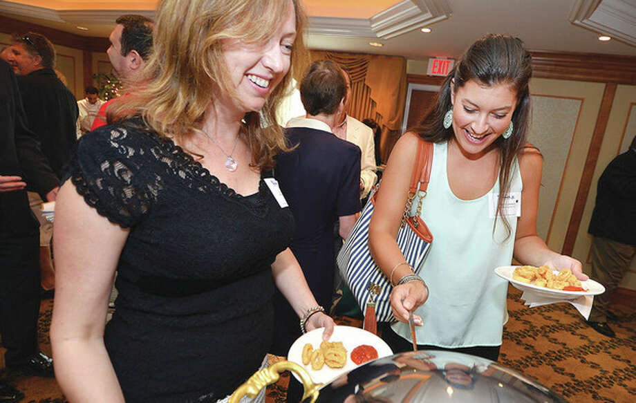Hour Photo/Alex von Kleydorff . New Chamber Members Ela Lagasse and Raven Cimmino with Belpointe Capitol, try some of the calamari during the New Member reception for the Norwalk Chamber of Commerce at The norwalk Inn and Conference Center