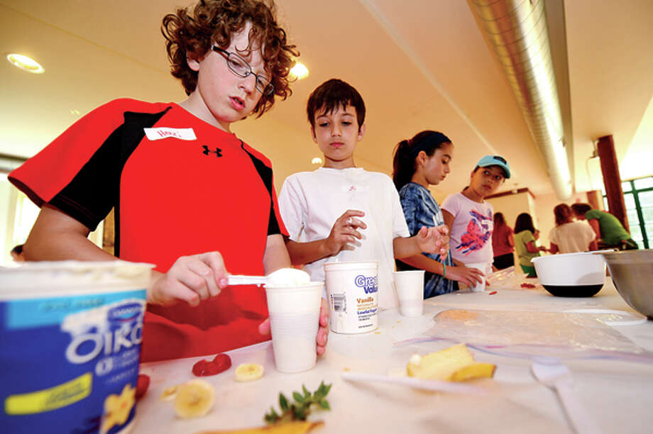 Campers Henri Connors and J.D. Meyer, both 12, make fruit parfaits as Ambler Farm begins its summer programs for preschoolers and students grades 1-7 this week through July. The programs introduce children to animals on the farm, harvesting, hayrides, woodworking and planting. Hour photo / Erik Trautmann / (C)2013, The Hour Newspapers, all rights reserved