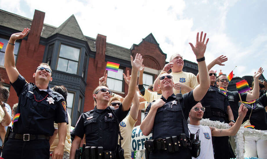 Members of the Chicago Lesbian and Gay Police Association wave to crowds during the Chicago Gay Pride Parade in Chicago, Sunday, June 30, 2013. (AP Photo/Scott Eisen) / AP