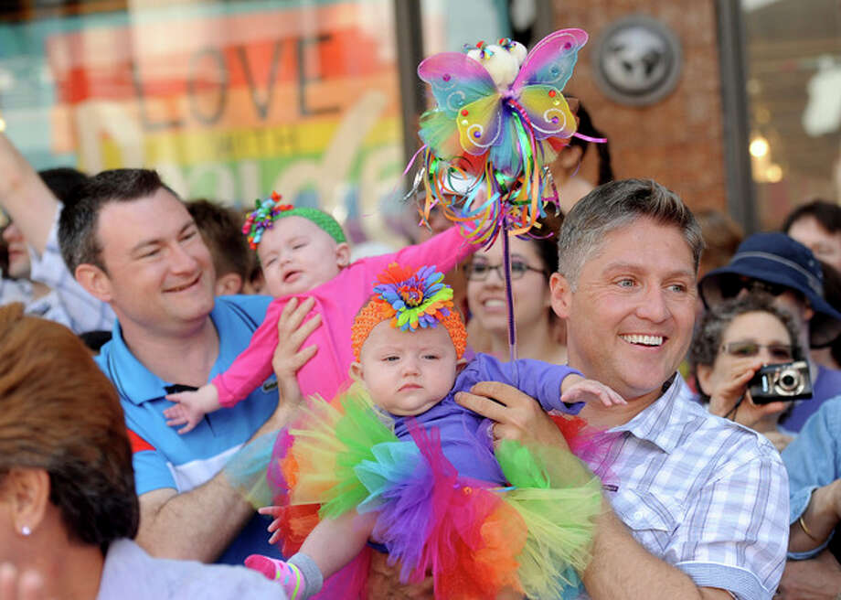 Tim, right, and Joseph Ginejko hold their 6-month-old twin daughters while watching San Francisco's 43rd annual Gay Pride parade Sunday, June 30, 2013. The couple, who traveled from Fresno, Calif. for the celebration, wed in 2008. (AP Photo/Noah Berger) / FR34727 AP
