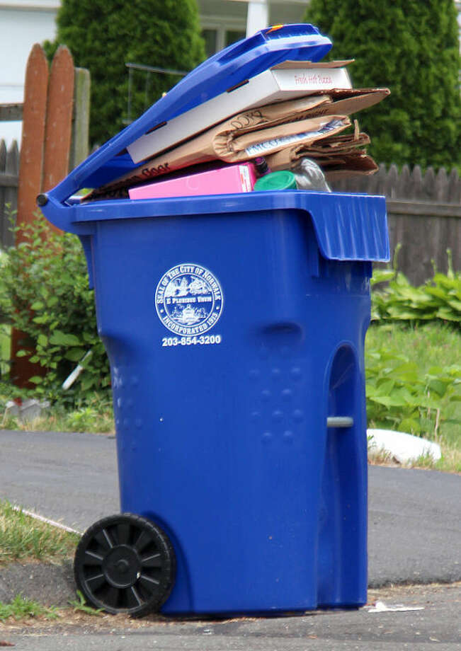 Hour photo / Chris Bosak Monday was the first day for single-stream recycling in Norwalk. Streets in the Spring Hill area of the city were lined with both the new arge blue recycling bins as well as the old smaller bins.