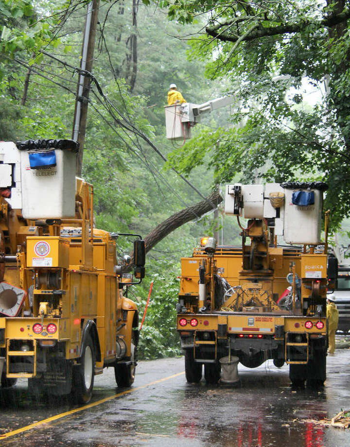 Hour photo / Chris Bosak Electrical crews work on Drum Hill Road in Wilton on Monday afternoon after heavy winds and rains knocked branches off trees and onto power lines, cutting electricity to nearby homes.