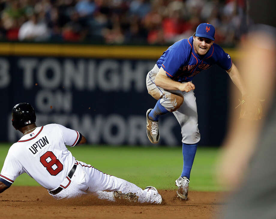New York Mets second baseman Daniel Murphy, back right, avoids Atlanta Braves' Justin Upton (8) while turning a a double play on a B.J. Upton ground ball in the seventh inning of a baseball game on Thursday, June 20, 2013, in Atlanta. (AP Photo/John Bazemore) / AP