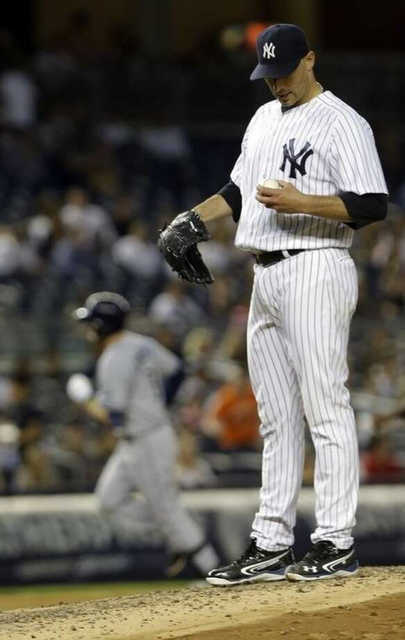 New York Yankees' Andy Pettitte reacts as Tampa Bay Rays' Evan Longoria runs the bases after hitting a home run during the sixth inning of a baseball game on Thursday, June 20, 2013, in New York. (AP Photo/Frank Franklin II)