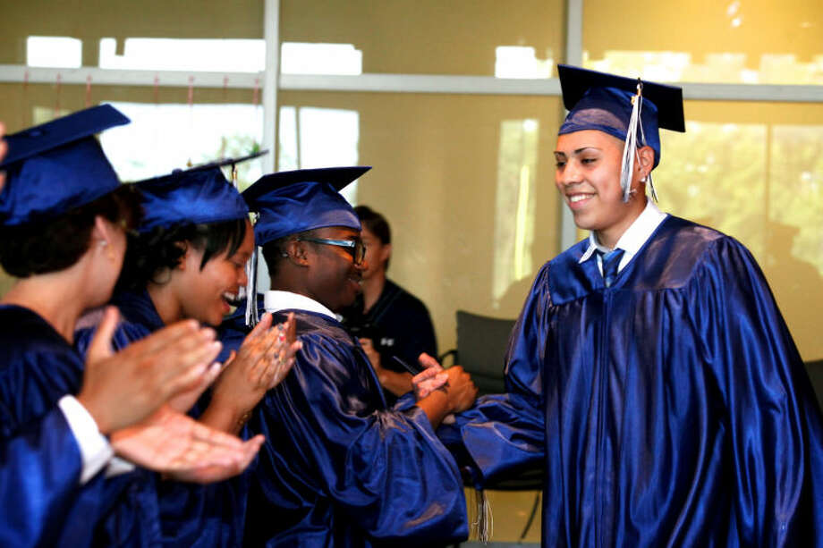 Valedictorian Alexis Ortega gives a high five to a classmate after giving his speech during Briggs High School's commencement ceremony held at Brien McMahon in Norwalk Thursday evening. Hour Photo / Danielle Calloway