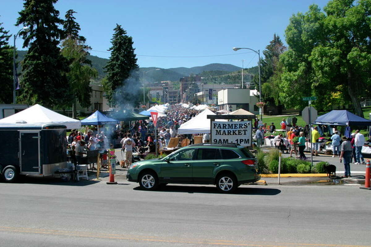 This June 15, 2013 photo shows the farmer?'s market in Helena, Mont., a Saturday morning institution. Buskers on violin and guitar provide the soundtrack as kids and dogs romp while neighbors stop to chat. You?'ll have to open your wallet to sample fare like cherries and kettle corn, but strolling around and people-watching is fun and free. (AP Photo/Montana Marketing Inc., Scott Peterson)