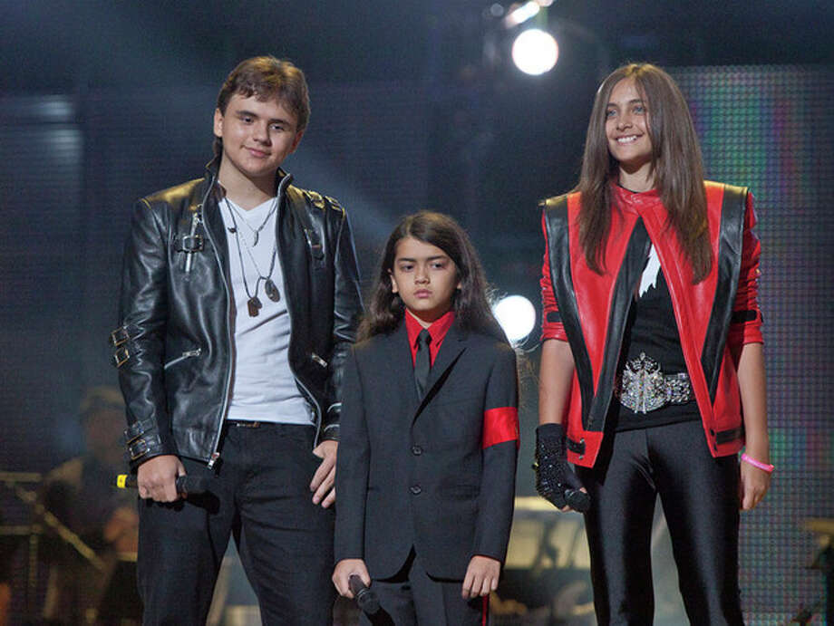 "FILE - In this Oct. 8, 2011 file photo, from left, Prince Jackson, Prince Michael II ""Blanket""Jackson and Paris Jackson arrive on stage at the Michael Forever the Tribute Concert, at the Millennium Stadium in Cardiff, Wales. Jurors hearing a civil case in Los Angeles filed by Jackson's mother, Katherine Jackson, have heard numerous stories about the entertainer's devotion to his children as expressed through extravagant birthday parties and secret family outings. The tender moments have been described throughout the trial, which concluded its eighth week on Friday, June 21, 2013. (AP Photo/Joel Ryan, file) *Editorial Use Only* / AP"