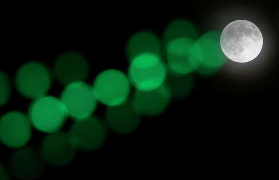 A full moon rises through a hazy sky past a string of green lights, Saturday, June 22, 2013, in Baltimore. The moon, which will reach its full stage on Sunday, is expected to be 13.5 percent closer to earth during a phenomenon known as supermoon. (AP Photo/Patrick Semansky) / AP