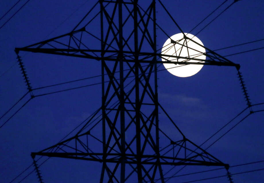 The moon rises behind power lines on Saturday, June 22, 2013, in Nashville, Tenn. The biggest and brightest full moon of the year, called a supermoon, happens as the moon passes closer to earth than usual. (AP Photo/Mark Humphrey) / AP