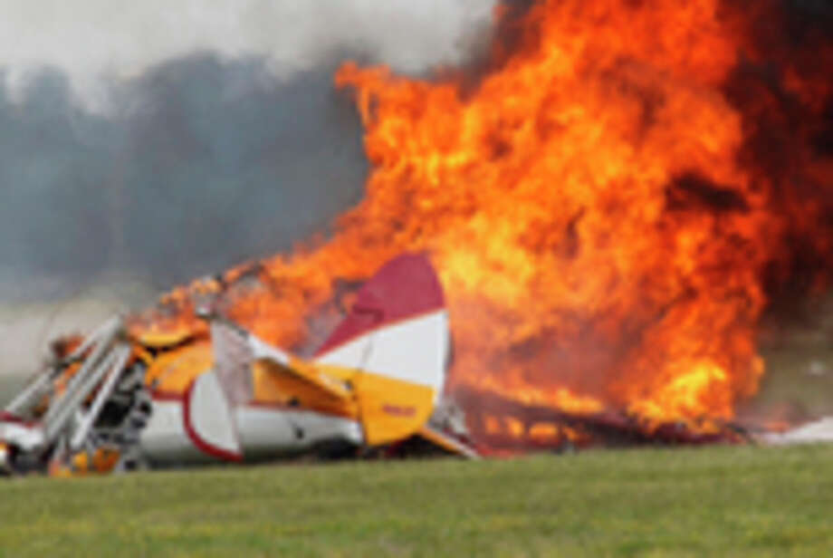 Flames erupt from a plane after it crashed at the Vectren Air Show at the airport in Dayton, Ohio, on Saturday, June 22, 2013. The crash killed the pilot and stunt walker on the plane instantly, authorities said. (AP Photo/Dayton Daily News, Ty Greenlees) / Dayton Daily News