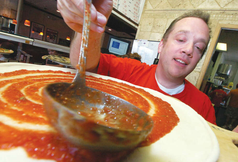 "Bruno DiFabio sauces up a pizza at Pinocchio Pizza in Wilton Center. DiFabio will be making pizzas as part of the event, ""A Slice for the Cure."""