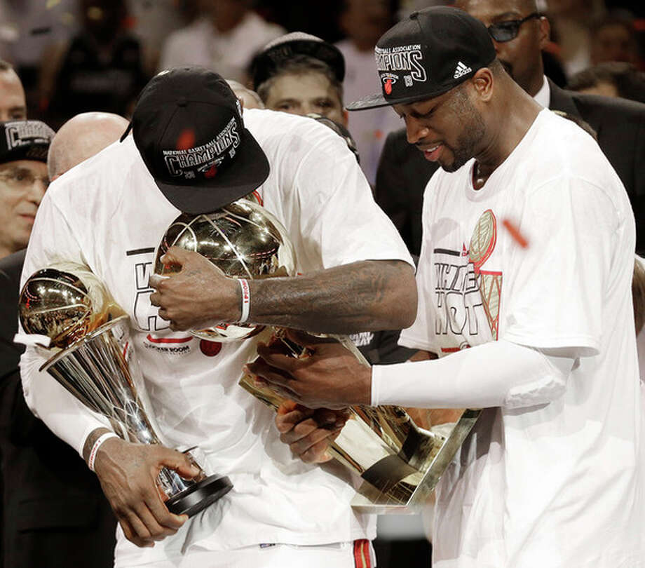 The Miami Heat's Dwyane Wade, right, holds the Larry O'Brien NBA Championship Trophy with LeBron James holding his Bill Russell NBA Finals Most Valuable Player Award after Game 7 of the NBA basketball championship game against the San Antonio Spurs, Friday, June 21, 2013, in Miami. The Miami Heat defeated the San Antonio Spurs 95-88 to win their second straight NBA championship. (AP Photo/Lynne Sladky) / AP